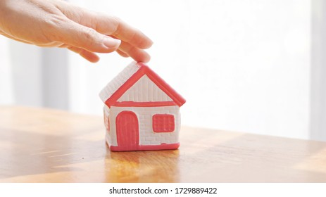 Hand modeled house Concept of buying a house, selling a house with house model on the desk