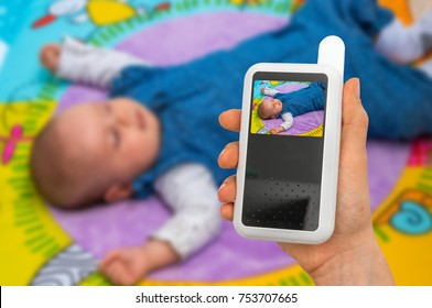 Hand of mother is holding baby monitor camera for safety of her cute baby