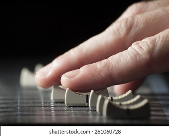 Hand moving  faders of the mixing desk, for music,sound,entertainment themes