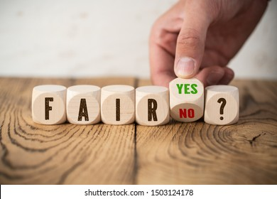 hand is moving one cube with options yes and no deciding between fair and unfair
