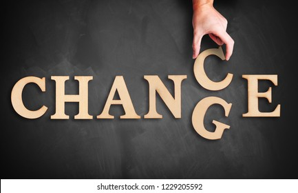 "hand is moving a wooden letter, turning the word ""change"" to ""chance"" on a blackboard"
