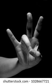 hand in mudra gesture on black background, monochrome