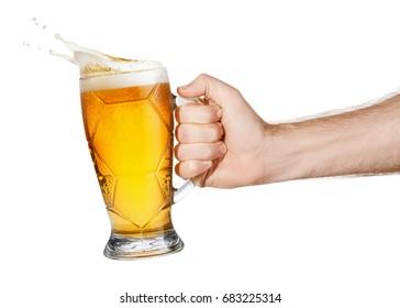 hand with mug of splashing beer isolated on white background