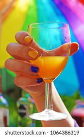 Hand with multi-colored nails holding a glass with a orange cocktail on the background of an rainbow umbrella on a bright sunny day.