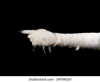 Hand of mummy indicates on dark gradient background. The horizontal position