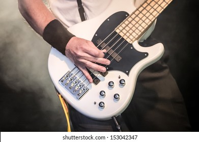 hand of a musician playing a five string bass guitar