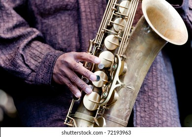 Hand of musician playing jazz saxophone during live performance on stage
