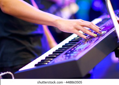 hand of musician playing keyboard in concert with shallow depth of field