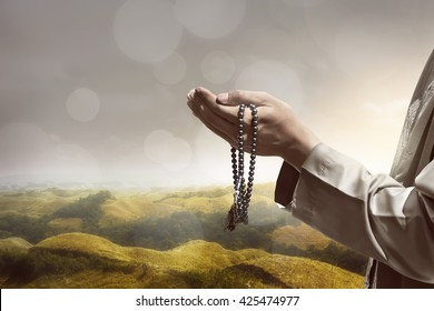 Hand of muslim people praying with hill landscape background