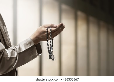 Hand of muslim people praying with mosque interior background