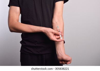 Hand of the narcotist preparing to inject drugs