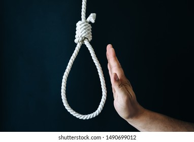 Hand near the noose on black background. Suicide concept. Hanging because of work stress. Depression of burnout. Terrible life situation.