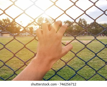 Hand with net in soccer field background,this image for loneliness concept.