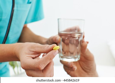 Hand of nurse with medicine and a glass of water