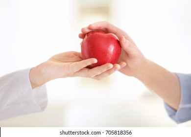 Hand of nutritionist giving apple to patient. Weight loss concept