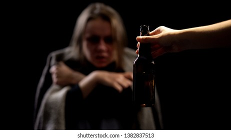Hand offering beer bottle to alcoholic woman, miserable life, addiction concept