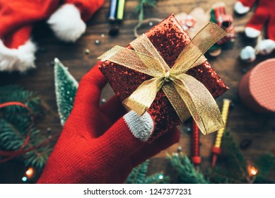 Hand offering Christmas gift wrapped in a box for cheerful holidays