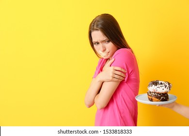 Hand offering to sad woman with taped mouth tasty donuts on color background. Diet concept