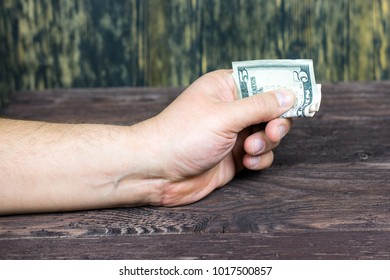 The hand offers dollars. bribe. corruption.