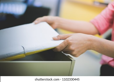 a hand of office employee choose and pick a folder of document paper from opened office's steel drawer