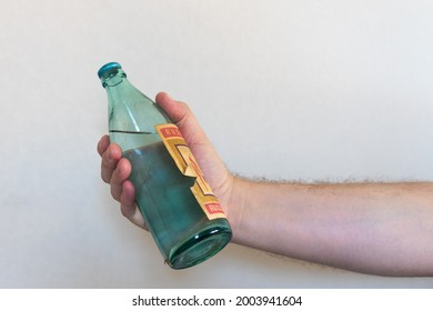 A hand with an old bottle of Russian vodka on a white background. Half a liter of vodka in your hand. The concept of alcoholism.