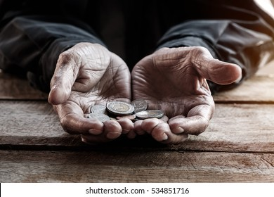 hand old man begging for money because of the hunger on the wood table. vintage tone