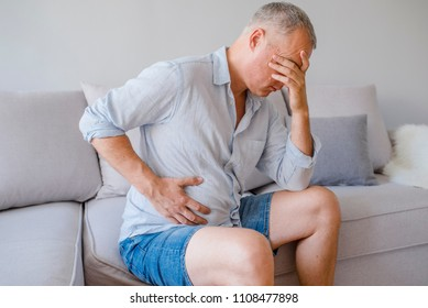 Hand of old man holding stomach suffering from pain, diarrhea, indigestive problem. A middle-aged man has a stomach ache. Unhappy man suffering from stomach ache at home