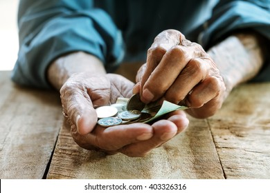 Hand the old man and pile coin for saving. money saving concept.