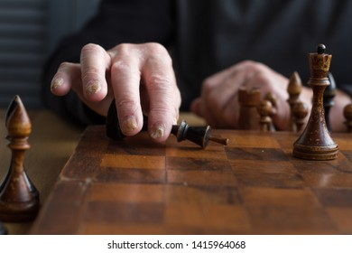 The hand of an old man puts a black king's figure on the board acknowledging loss, concept business games, selective focus, copyspace