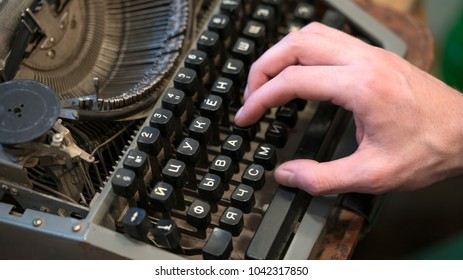 hand and an old typewriter