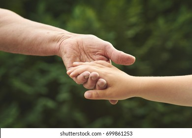 Hand in hand. Old woman hold her young grandchild's hand