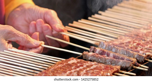 hand of old woman and raw meat called Arrosticini in Italian Language