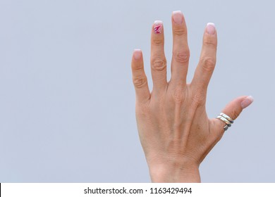 Hand of an older woman with manicured nails wearing a silver thumb ring with splayed fingers over a white background with copy space