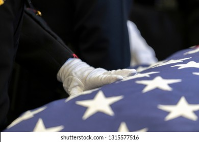 Hand on American Flag draped on a casket of a Fallen Hero.