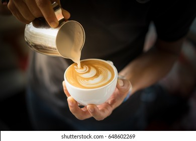 Hand on Barista making latte cafe, Cup of coffee with beautiful Latte art on white cup