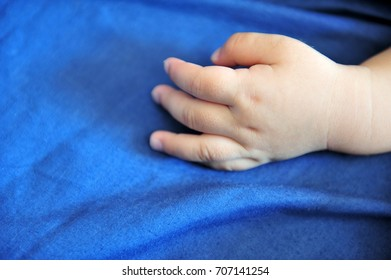 Baby's hand on bed with copy space