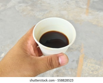Hand on black coffee in white cup.