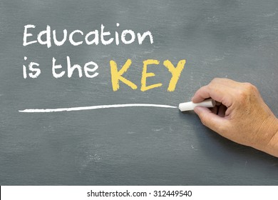Hand on a chalkboard with the words Education is the key. Education class concept showing teacher hand writing on the blackboard.
