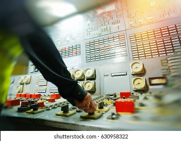 Hand on the control panel of a power plant