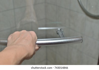 Hand on a door handle of a glass shower cabin in order to open or close it