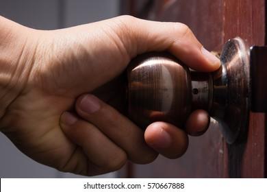 Hand on door knobs, Open door knobs