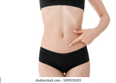 Hand on fit slim woman belly. Perfect sports body of woman in black lingerie isolated on white background.