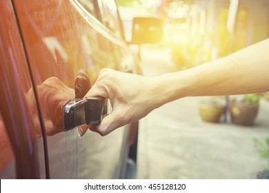 Hand on handle. Close-up of man in informalwear opening a car door,vintage color,morning light ,selective focus