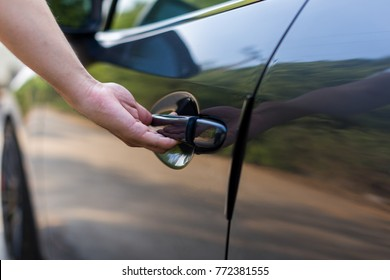 Hand on handle. Close-up of man hand opening a car door