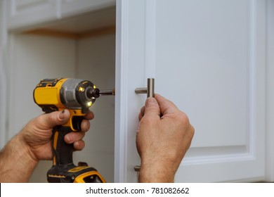 Hand on handle installation door in kitchen cabinet with a screwdriver