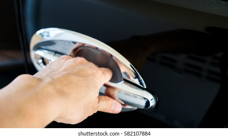 Hand on handle, a man try to open a car