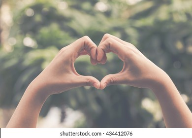 Hand on heart-shaped bokeh background blurred, natural tones vintage style. Show the world you love Love Family between two people.Let's Stay Together happy mother's day,