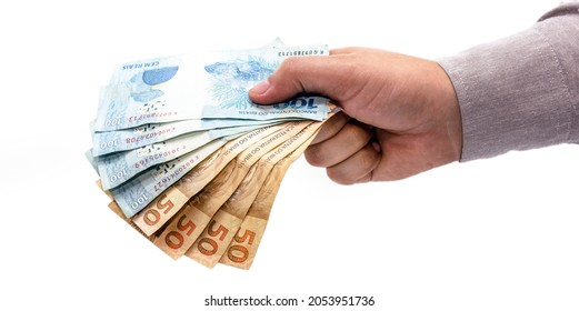hand on isolated white background offering brazil money, one hundred and fifty reais banknotes, brazilian economy.