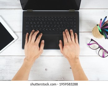 Hand on keyboard laptop workspace on the desk with tablet galsses and pencil box top view