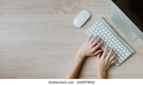 hand on keyboard on office working table,working day on the wooden table